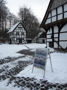 Ausstellungsplakat am verschneiten BauernhausMuseum Bielefeld